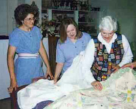 Sewist repairing quilts in the atelier